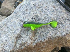 Grüner Gummifisch mit Bleikopf auf Stein